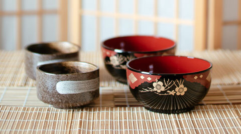 red and black Japanese lacquer bowls and brown earthen tea cups